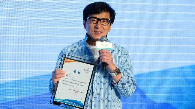 Jackie Chan pri preberaní certifikátu za spoluúčasť na tvorbe piesne pre kandidatúru Pekingu na usporiadanie ZOH 2022